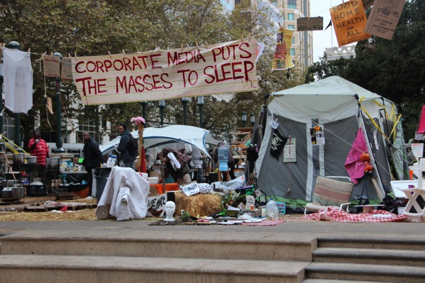 """corporate media puts the masses to sleep"" banner at early occupy oakland circa october"