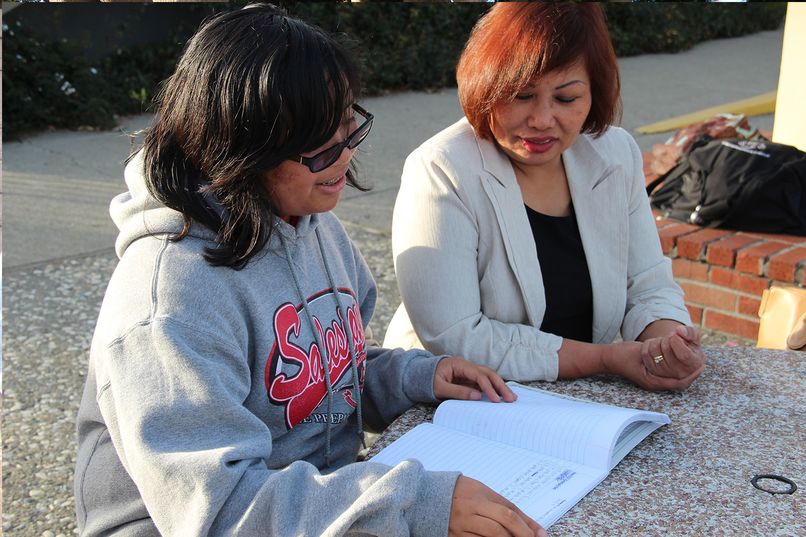"Nurse Angie Gayoso (right) looks at Allyson's school assignments: ""She reads a lot of books and always gets straight A's,"" she says of her daughter."